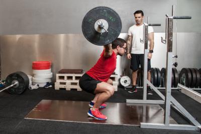 Personlig trener ser på sin elev som gjør styrkeløft.